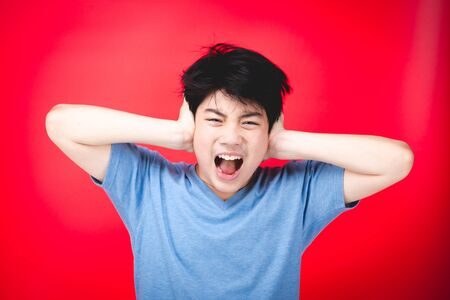 Portrait of asian little boy Upset and angry , concept for anger, frustration and mischief. isolate on red background. Stockfoto - 132079233