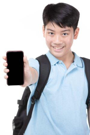 Asian student boy with backpack and stationery holding cell phone isolated on white background. Back to school concept. Banque d'images - 132044654