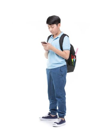 Asian student boy with backpack and stationery holding cell phone isolated on white background. Back to school concept. Banque d'images - 132044655