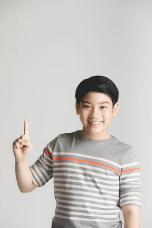 Half-length emotional portrait of asian young boy. Funny teenager pointing and looking camera while smiling, isolated on gray background. Handsome happy child pointing up