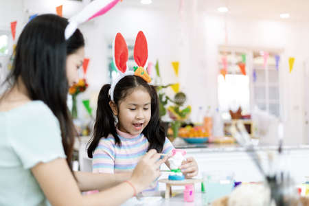 Asian kindergarten school girl with mother painting Plaster doll with Acrylic water color paint in living room at home. Homeschooling and distance learning.