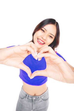 Cheerful beautiful girl making heart by hands isolated on a white background. Female hands making sign Heart by fingers,