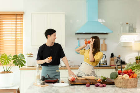 Young asian happy active family couple dancing laughing together preparing food at home, carefree joyful husband and wife having fun cooking healthy romantic dinner meal listen to music in kitchen.