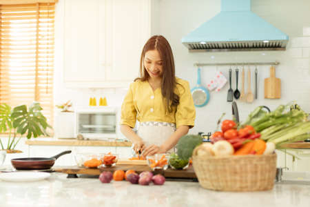 Woman cooking rice with vegetables in kitchen with sun light.
