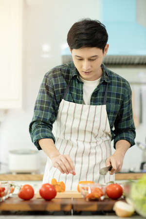 Man cooking with vegetables in kitchen