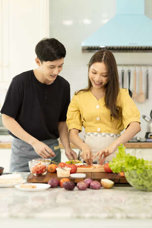 Portrait young couple in love helping to cook In a romantic atmosphere at home with smile face. Banco de Imagens
