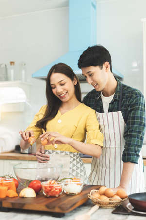 Portrait young couple in love helping to cook In a romantic atmosphere at home and looking at camera with smile face. Banco de Imagens