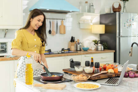 A beautiful Asian girl makes breakfast by looking at how to make it with her laptop computer with a happy face. At her own house Banco de Imagens