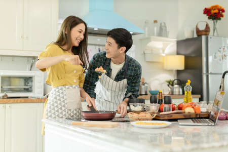 Portrait young couple in love helping to cook In a romantic atmosphere at home and looking with smile face.