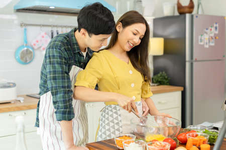 A couple breaks an egg to make a morning omelet at home. Romantic time For a newly married couple.