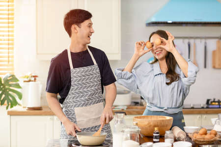 Asian couple Help each other to make a bakery In a romantic atmosphere in the kitchen at home. Young women help cook holiday with smiling and happy faces. Banco de Imagens