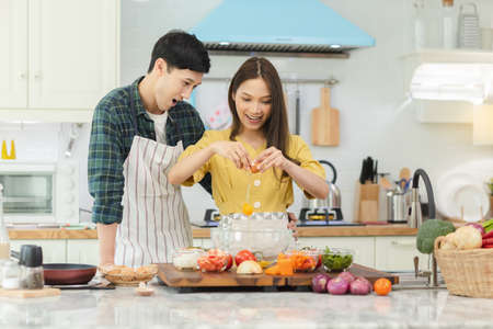 A couple breaks an egg to make a morning omelet at home. Romantic time For a newly married couple. Banco de Imagens