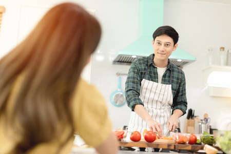 Husband slicing vegetables to prepare breakfast. With a young wife supporting him In a romantic atmosphere