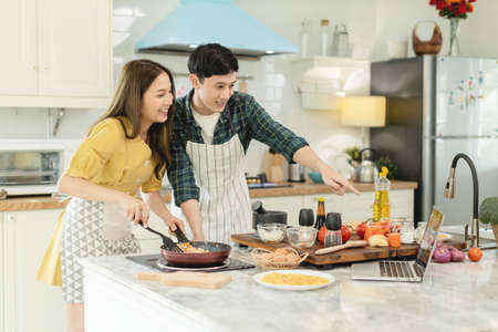 Young married couple Cooking breakfast By looking at how to make a laptop computer with a happy expression In their own home