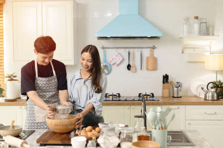 Asian couple Help each other to make a bakery In a romantic atmosphere in the kitchen at home. Young people work together to mix the ingredients in a wooden bowl before stirring them together. Banco de Imagens