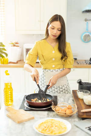 Woman cooking rice with vegetables in kitchen