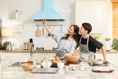 A couple uses their smart phone to take a picture while admiring his wife's cooking work With a happy face in an atmosphere of love Banco de Imagens