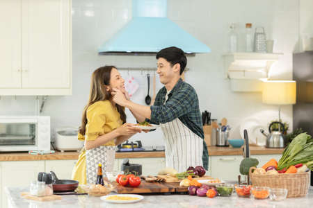 Portrait young couple in love helping to cook In a romantic atmosphere at home.