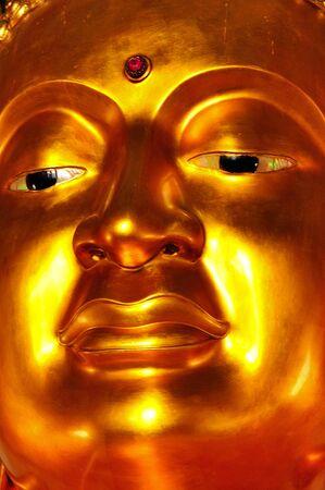 Diagonal close up of golden buddha face photo