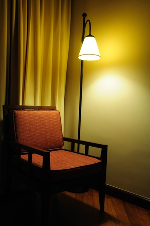 Chair and lamp bulb in dark room  photo