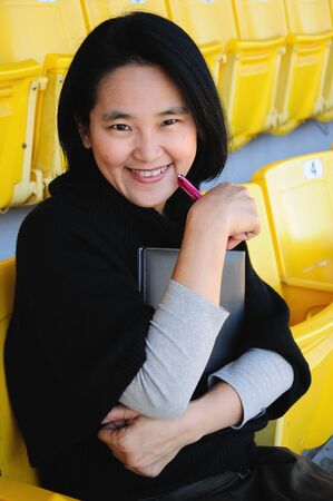 Young Asian college girl with a book sitting on grandstand Stock Photo - 13931373