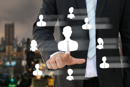 job recruitment: Businessman pointing people icon of human resources in business concept with city background