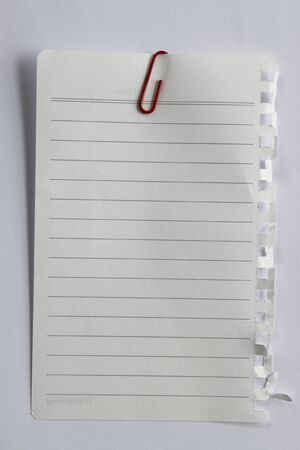 Blank note paper and red paper-clip. Isolated with clipping path. photo