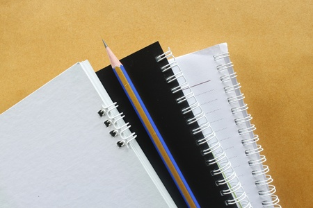 3 notebook one pencil on brown background Stock Photo - 10137036