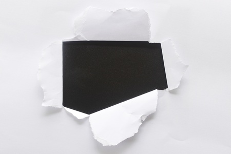 a hole torn in a piece of paper photo