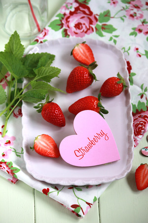 Strawberry heart on wooden background photo