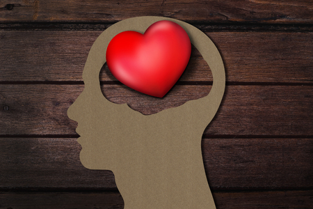 temperament: Human head paper cut with 3d Red Heart instead the Brain, Present over Wooden Background Stock Photo