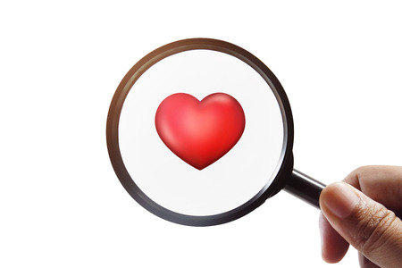 looking for love: Hand holding magnifying glass to looking for red 3d heart,find true love concept Stock Photo