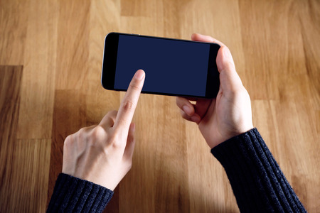Female holding Smart Phone Mockup image by Hand and showing a mobile with blank screen over wooden desk
