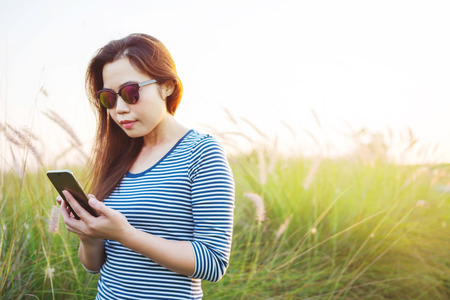 Female wearing sunglasses and using Smart Phone to text a message at meadow