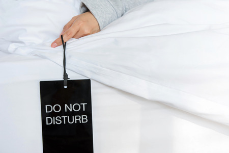 subjective: Female holding Sign tag : Do not disturb while Sleep in Bedroom Stock Photo