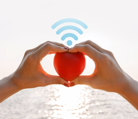 Connect or spread love concept, Hand of female raised up red heart over the summer sea with wifi icon