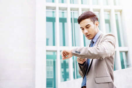 Young Businessman seeing his watch with worrying face outside, Time in business concept, Focus on hand, Office buiding as background