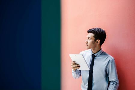 若くて最新魅力的なビジネスマンだと思うとカラフルな壁、通信、メッセージまたは使用技術ビジネス仕事の概念で現代の男性のライフ スタイルで 写真素材
