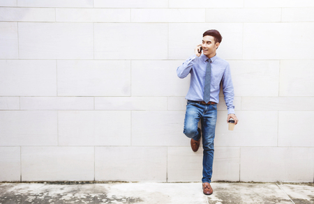 Young and modern attractive Businessman stand and talk via Smart phone outside building wall, Social communicate technology in business concept, Lifestyle of modern male