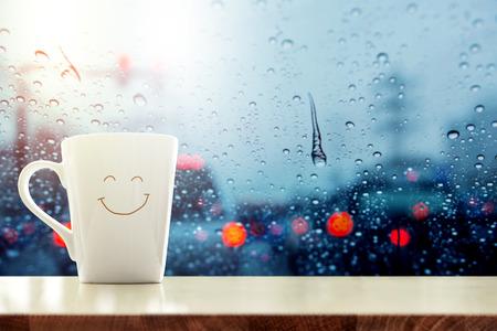 Blije koffiemok met smilley gezicht op bureau binnen glasvenster, Wazig verkeersopstoppinglicht in stad als buitenmening, Ontspannend in koffie op regenachtige dag Stockfoto