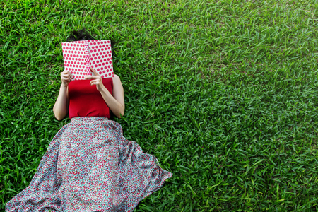 Woman lay down or relaxing on green grass reading book in summer or spring, top view Stock Photo