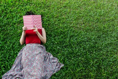 女人躺下或放松在绿色的草地上看书,在夏季或春季,俯视图