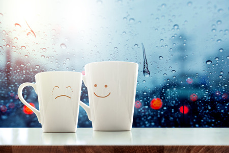 Its ok concept, Friend of  Coffee Mug with Sadness crying face cartoon and kindness happy face inside the room, Blurred city light and rain drop in city as outside view through glass window