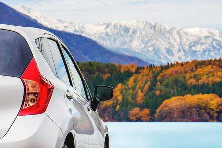 道路旅行コンセプト、車運転旅秋のシーズン、湖、美しい紅葉と背景に雪で覆われた山々