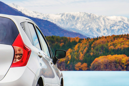 Road Trip Concept, Car Driving Travel in Autumn Season, Lake, beautiful Foliage and Mountains covered by Snow as background Banco de Imagens