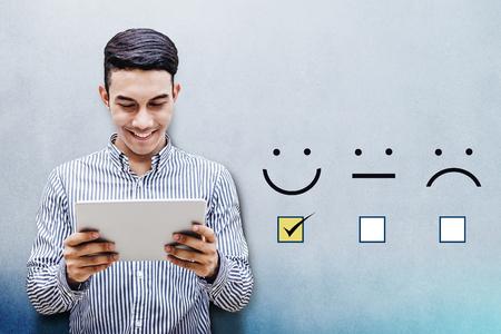 고객 경험 개념, 행복 한 실업가 만족스러운 설문 조사를위한 우수 스마일 얼굴 등급에 체크 상자가있는 디지털 타블렛 잡고