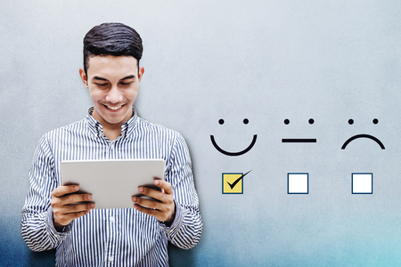 Customer Experience Concept, Happy Businessman holding digital Tablet with a checked box on Excellent Smiley Face Rating for a Satisfaction Survey Stockfoto