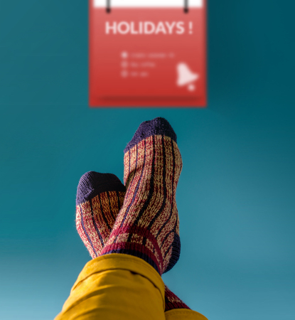 Waiting for Holidays Concept, Part of Human Legs with Knit Wool Socks in Relaxing posture on the Table, Blurred Red Calender as background