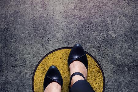 Concepto de zona de confort, mujer con zapatos de cuero pasos sobre la línea del círculo al límite exterior, vista superior y tono oscuro, piso de hormigón sucio grunge como fondo