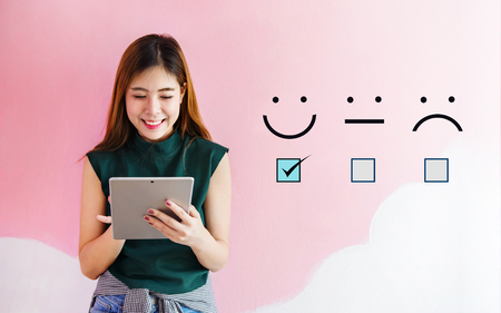 Customer Experience Concept, Happy Client Woman holding digital Tablet with a checked box on Excellent Smiley Face Rating for a Satisfaction Survey 版權商用圖片